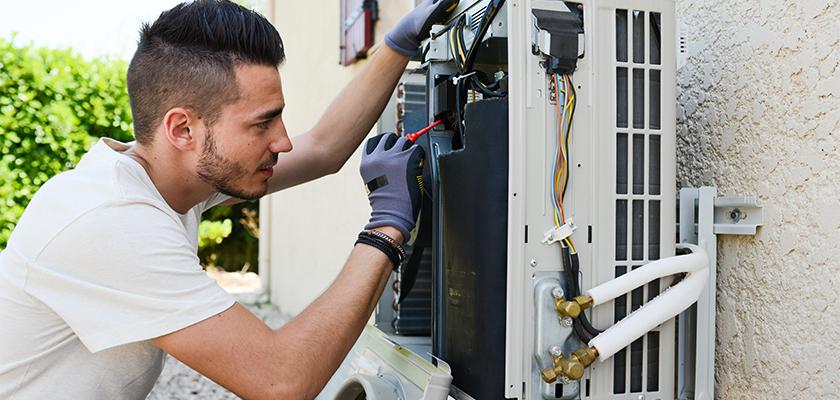 Man replacing broken air conditioner | SHW Blog