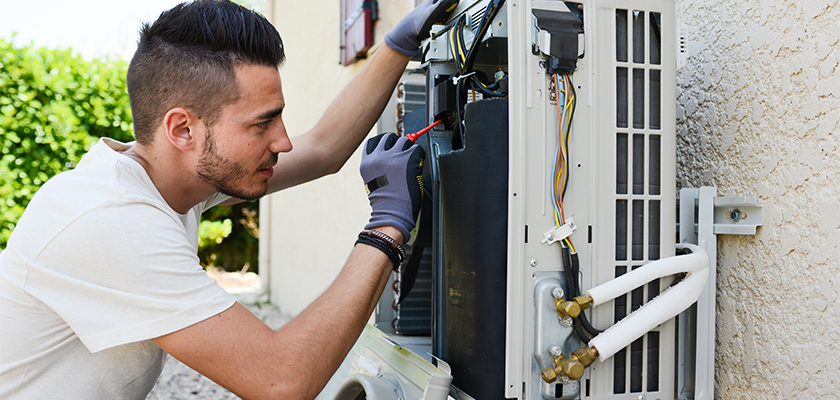 Man replacing broken air conditioner | SHW Blog
