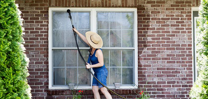 Woman washing windows for spring maintenance | SHW Blog