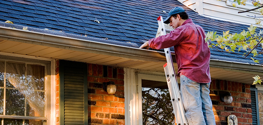 Man inspecting gutters to determine need for replacement | SHW Blog