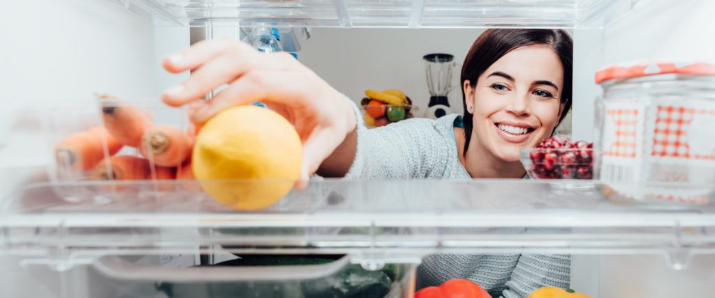 Smiling woman taking a fresh lemon out of the fridge thanks to her home warranty. | SHW Blog